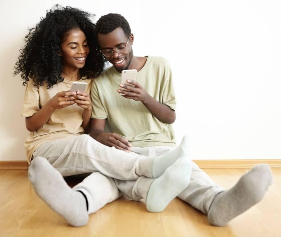 Casal sentado no chão mexendo em seus celulares.