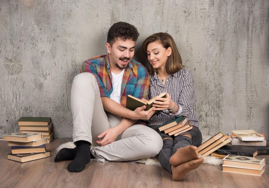Casal sentado no chão, encostados na parede, lendo um livro. Em volta deles estão outros livros empilhados.
