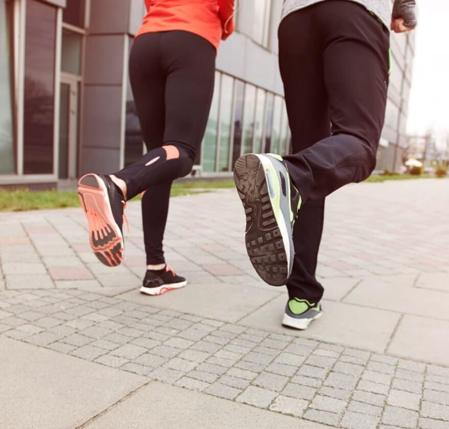 Casal correndo, foto tirada pelas costas, mostra apenas da cintura para baixo.