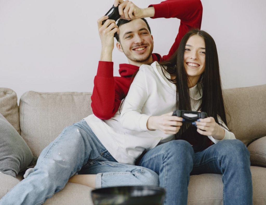 Casal sentado no sofá jogando video game.