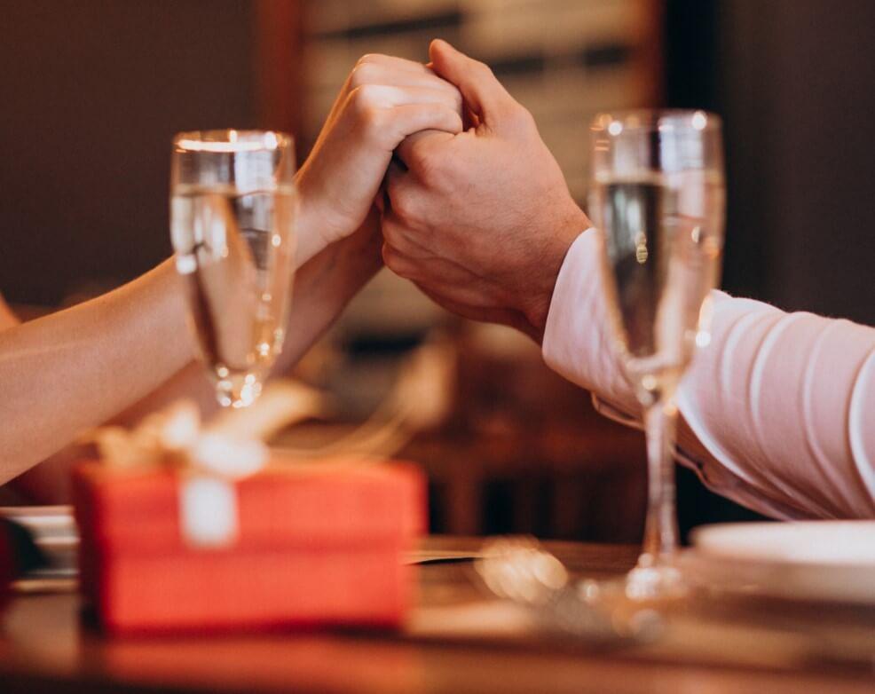 Mesa com uma caixa de presente e duas taças de espumante. No fundo um casal de mãos dadas, aparecendo apenas os braços e as mãos.