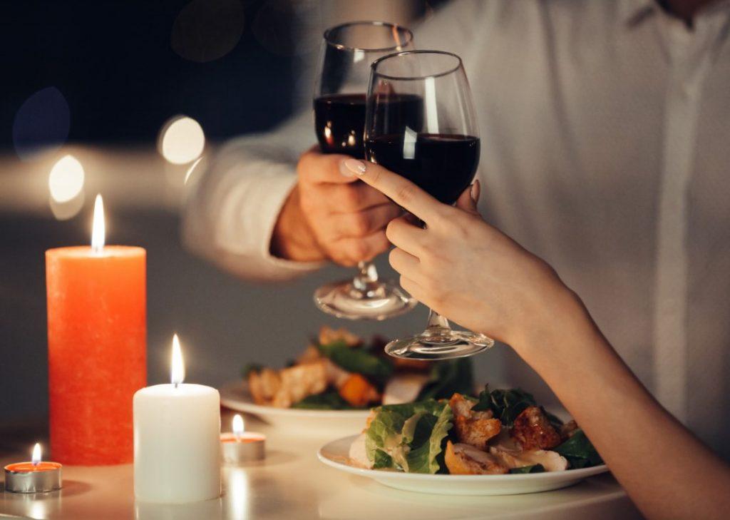 Mesa de jantar com pratos de comida, velas e um casal segurando taças de vinho, brindando.