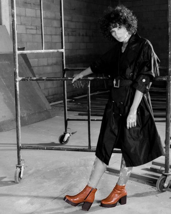 Modelo apoiada em um andaime, em um cenário rustico. Ela está usando um sobretudo de couro e uma bota de salto baixo, marrom.