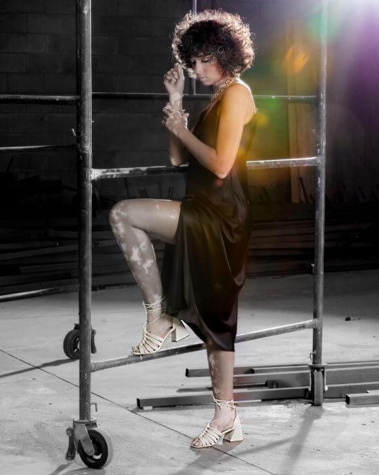 Modelo apoiada em um andaime, usando um vestido social midi e um salto alto bege.