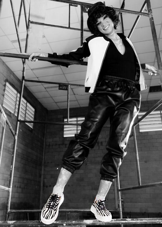 Modelo pendurada em um andaime, vestindo calça jogger, camiseta gola V e jaqueta. Nos pés, um tênis com estampa animal print.