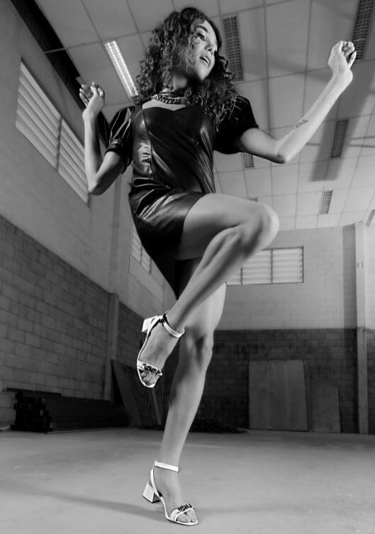 Modelo em um cenário rustico, dançando. Ela veste um vestido curto e um salto alto baixo branco.