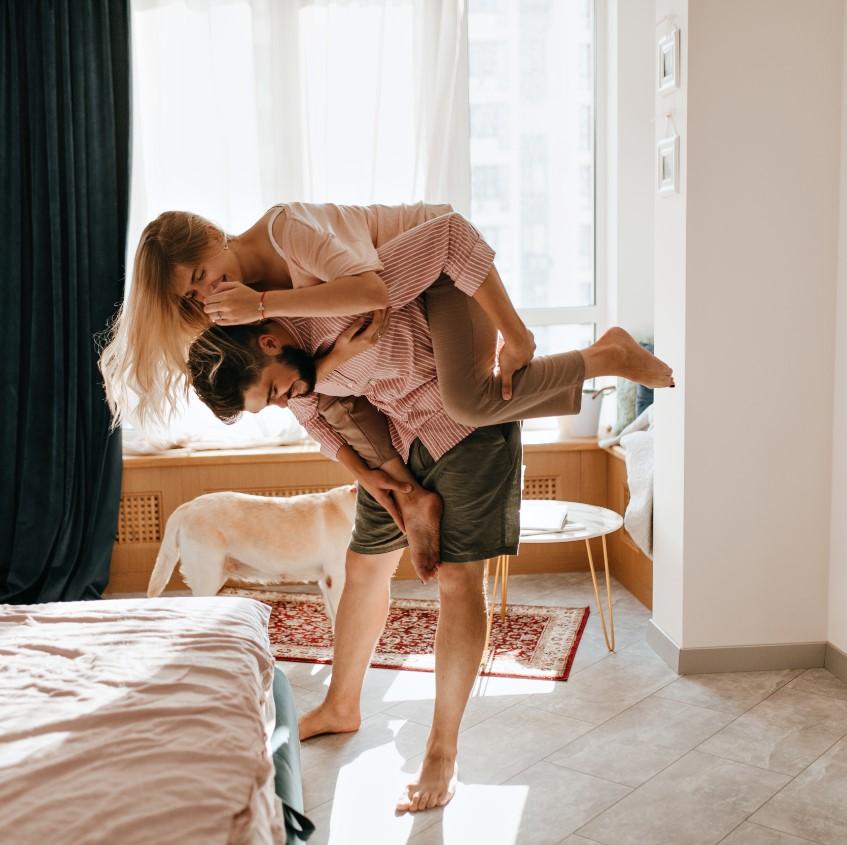 Casal no quarto, estão brincando e um cachorro observa no fundo.