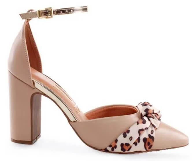 Sandália salto alto grosso, com bico fino, na cor bege. Possui enfeite de laço em tecido com estampa animal print.