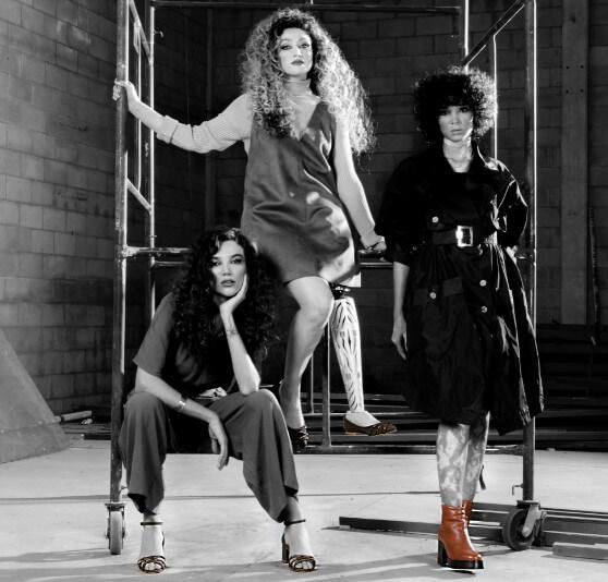 Três modelos mulheres apoiadas em um andaime de construção, em um cenário rustico. Imagem em preto e branco.