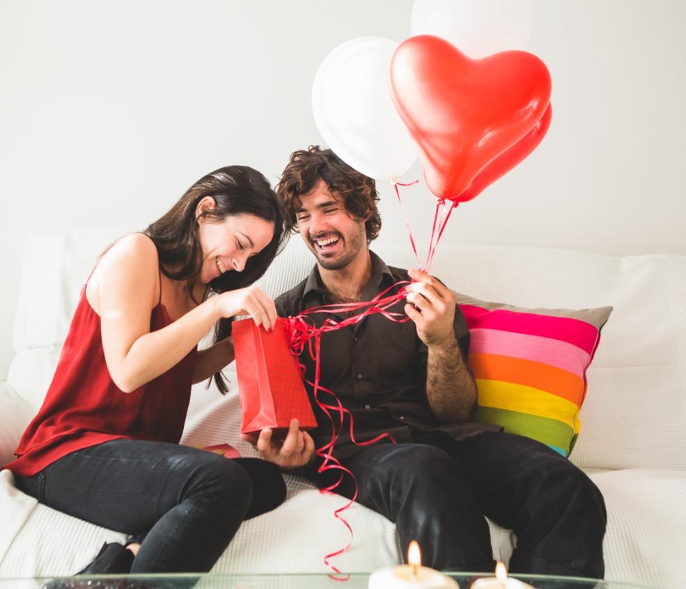 Casal sentado no sofá, a moça está abrindo presentes e o rapaz segurando balões em formato de coração.