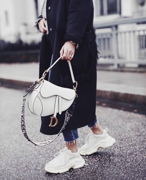Mulher na rua, vestida com calça jeans, sobretudo preto e tênis branco. Carregando uma bolsa branca, com alça  com detalhes em pedraria.