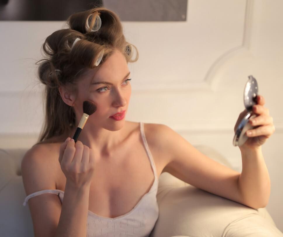Moça se maquiando, sentada no sofá. Está com pincel de base e um espelho pequeno redondo. Com bobs no cabelo.