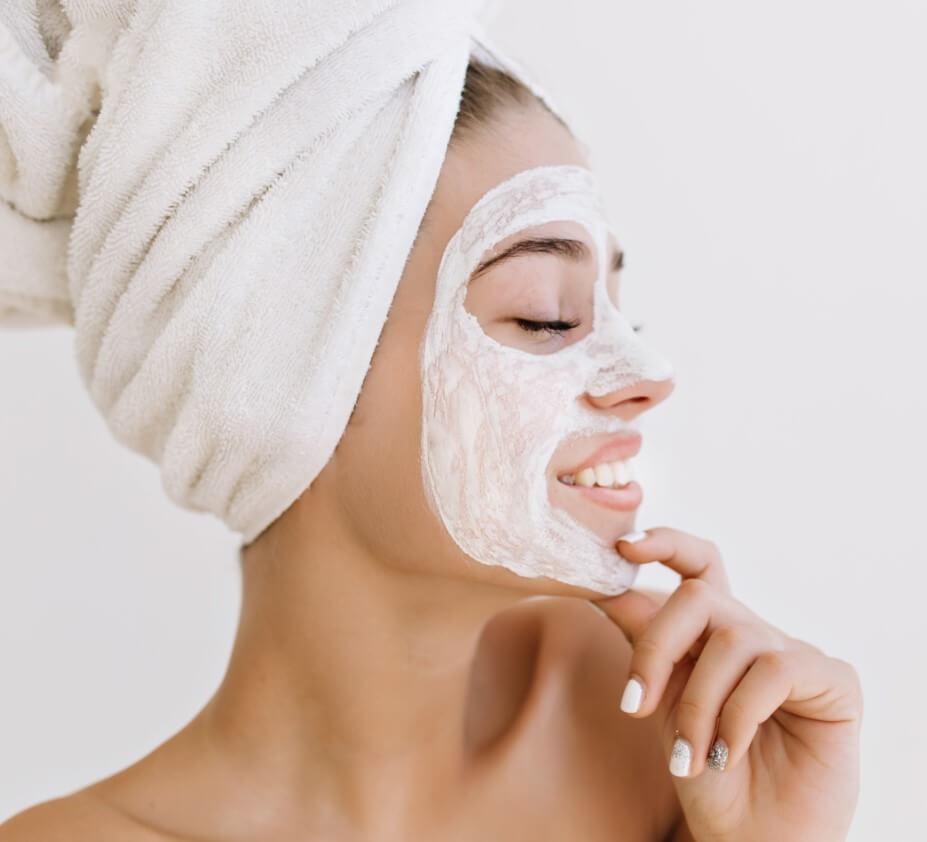 Moça com toalha enrolada na cabeça e creme no rosto.