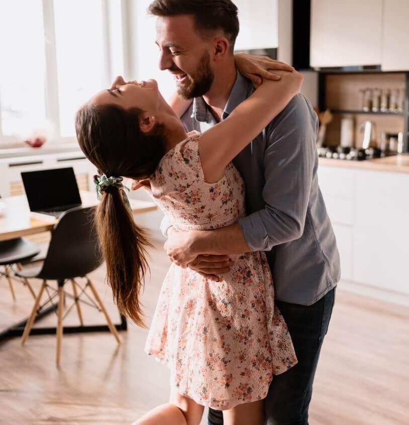 Casal dançando na cozinha.