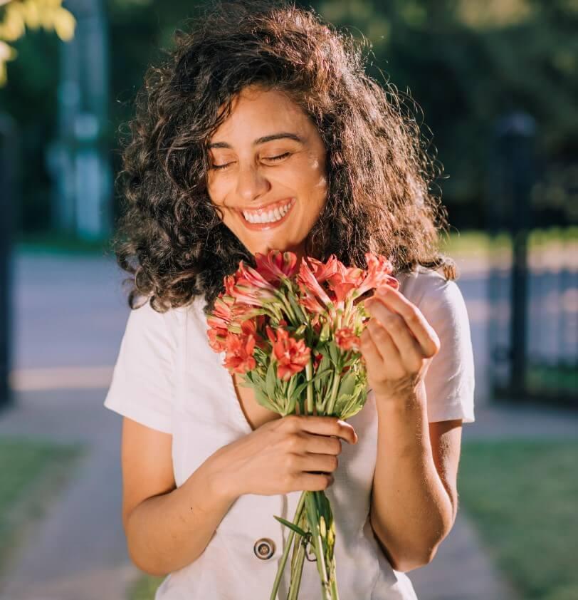 Moça em um quintal com gramado, segurando um buque de flores.