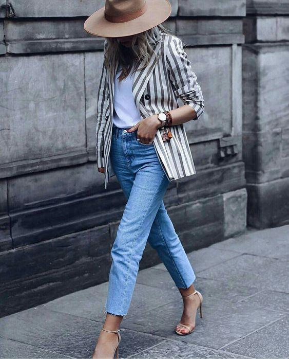 Mulher com modelo de blazer listrado, calça jeans e salto fino bege.
