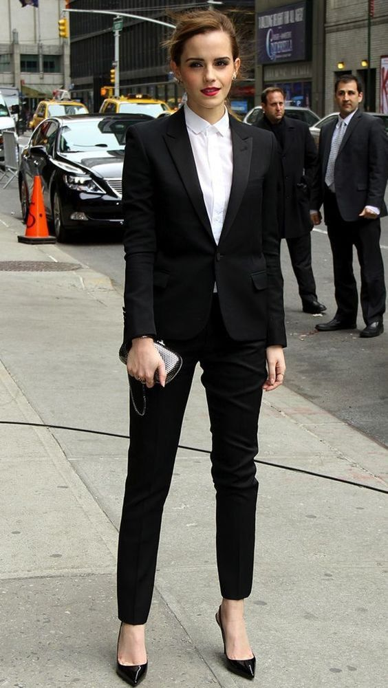 Emma Watson em uma rua movimentada, usando um terno preto. com salto fino preto.