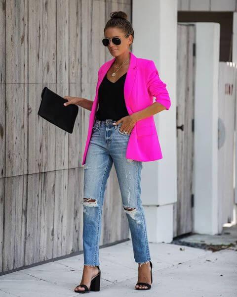 Mulher com blazer pink, calça jeans e salto alto grosso preto.