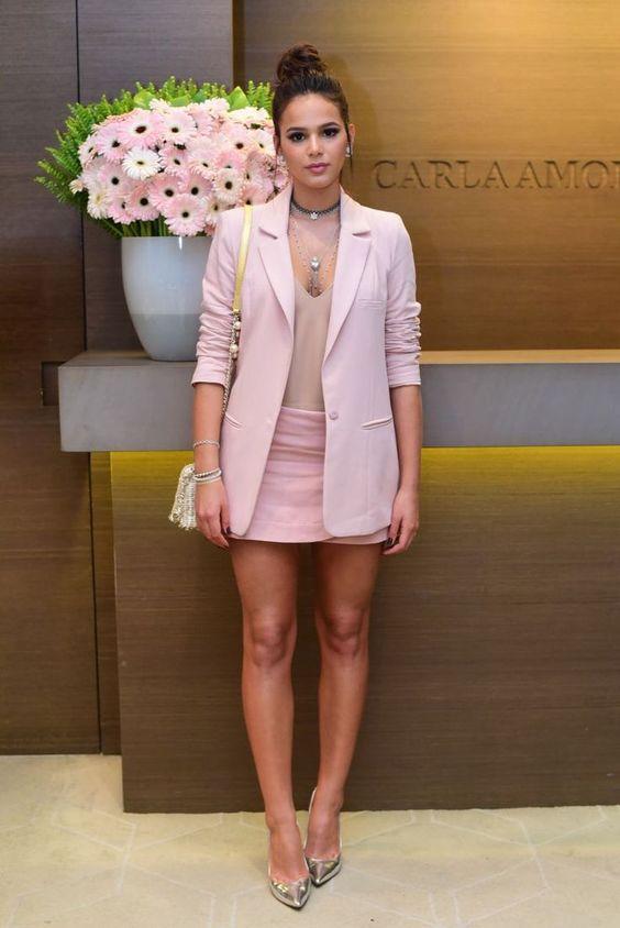 Bruna Marquezine com blazer rosa claro, saia rosa e salto alto dourado.