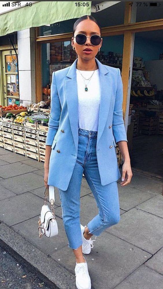 Mulher com blazer azul claro, calça jeans e tênis Chunky branco.