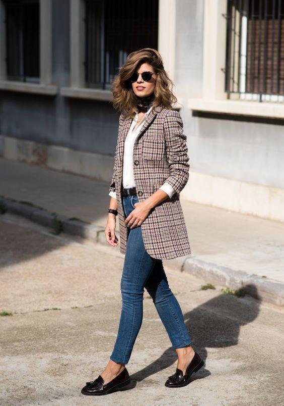 Mulher com maxi blazer xadrez, calça jeans e mocassim preto.