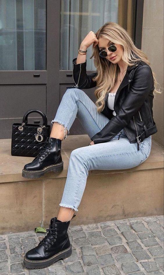Mulher com jaqueta de couro e coturno preto.
