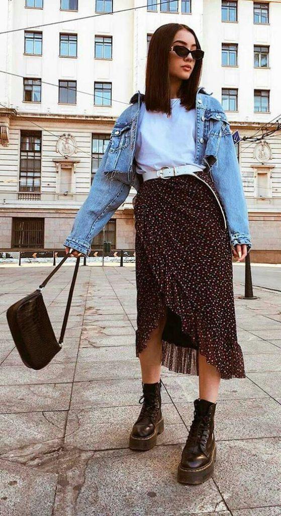 Mulher com saia midi, jaqueta jeans e bota coturno preta.