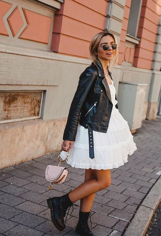 Mulher de vestido branco, jaqueta de couro e coturno preto.