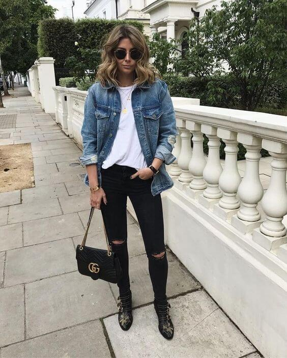 Mulher com jaqueta jeans e bota preta.