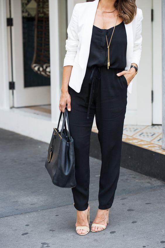 Mulher com blazer branco, macacão preto e sandália salto bloco, cor bege.