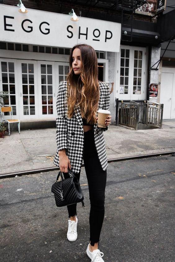 Mulher com maxi blazer xadrez, top e calça pretos, tênis branco.