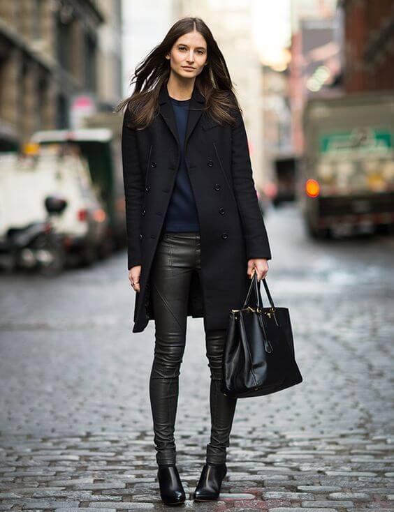 Mulher com calça preta, casaco azul escuro e bota cano baixo preta