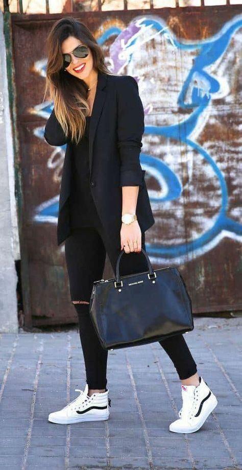Mulher com look todo preto e tênis branco.