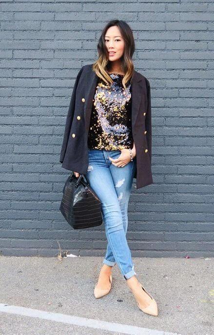 Mulher com camiseta florida, casaco preto, calça jeans clara e sapatilha nude de bico fino